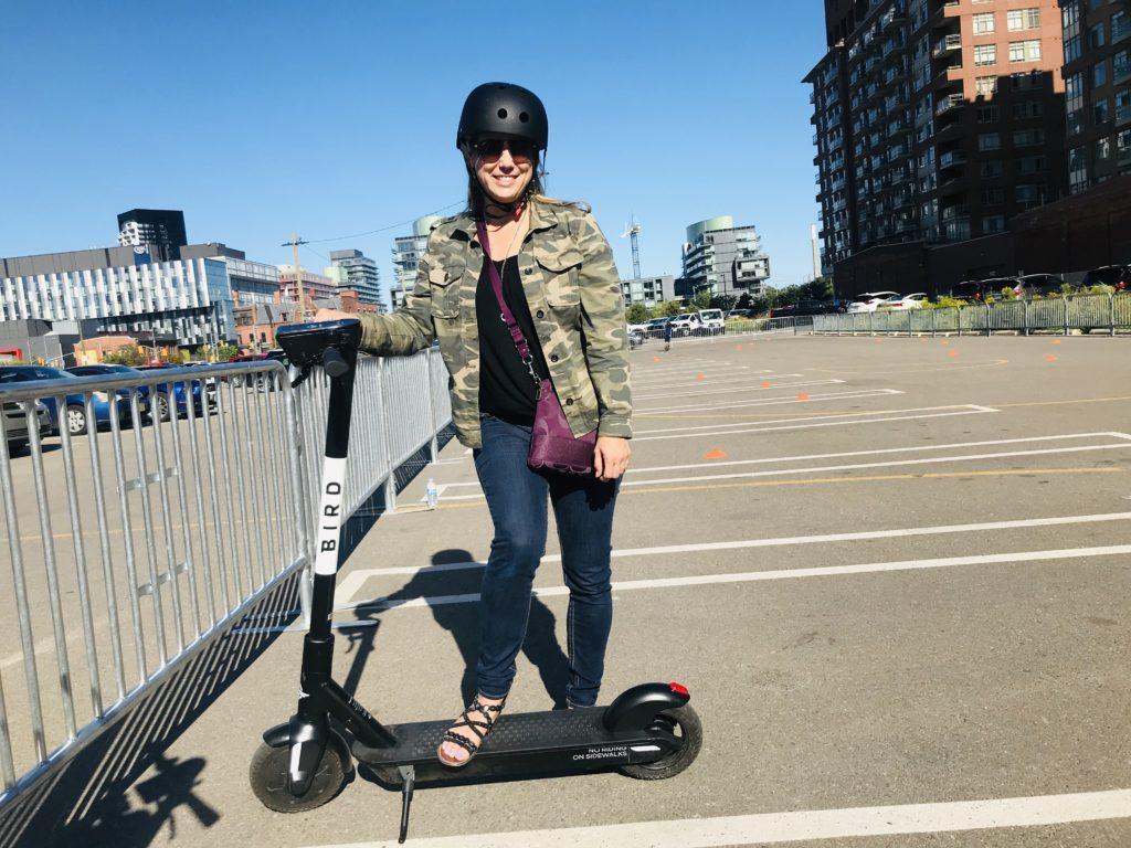 Woman standing beside a bird scooter